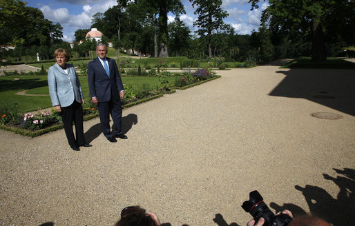 President George W. Bush and Germany's Chancellor Angela Merkel pause for photos during a walk in the garden Wednesday, June 11, 2008, during the President's visit to Schloss Meseberg, north of Berlin. The President met with Chancellor Merkel for a day of meetings before continuing his European visit with a stop in Rome. White House photo by Eric Draper