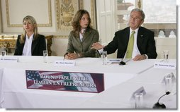 President George W. Bush gestures as he addresses participants at a roundtable meeting on business exchanges between Italy and the United States Thursday, June 12, 2008, at the Villa Aurelia in Rome. President Bush is seated next to entrepreneurs Valentina Coccoli, left, and Micol Macellari, center.  White House photo by Eric Draper
