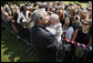 President George W. Bush gives a kiss to a baby during his greeting with members of the U.S. Mission in France, Saturday, June 14, 2008, at the Ambassador's residence in Paris. White House photo by Eric Draper