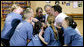 President George W. Bush participates in a basketball game huddle with members of the Peace Players basketball team and their coach Monday. June 16, 2008, during a visit to the Lough Integrated Primary School in Belfast, Ireland. White House photo by Chris Greenberg