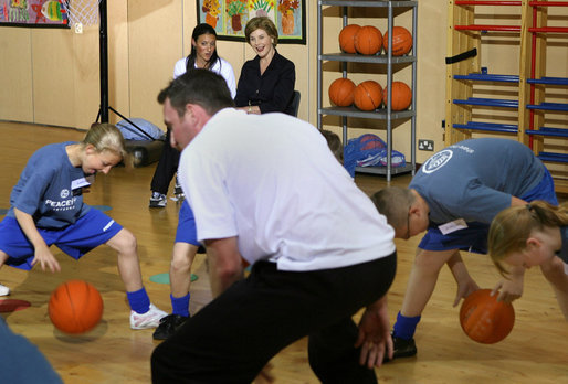 Mrs. Laura Bush watches a basketball demonstration at the Lough View Integrated Primary School's Gym in Belfast, Northern Ireland, June 16, 2008, during her visit to the school with President Bush. White House photo by Shealah Craighead