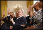President George W. Bush joins guests in clapping and waving to the music during performances in the East Room of the White House Tuesday, June 17, 2008, in honor of Black Music Month. White House photo by Eric Draper