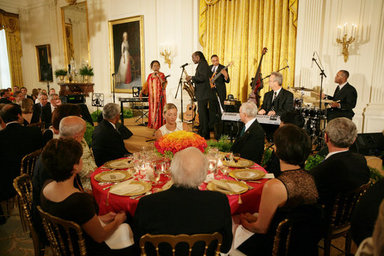 President George W. Bush joins invited guests Thursday evening, June 19, 2008 to the East Room of the White House, listening to vocalist Esther Williams and saxophonist Davey Yarborough during a social dinner in honor of American jazz. White House photo by Chris Greenberg