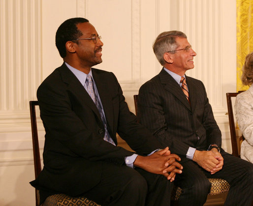 Dr. Benjamin Carson, left, seated with Dr. Anthony S. Fauci, listens Thursday, June 19, 2008, as he is announced as a recipient of the 2008 Presidential Medal of Freedom, at ceremonies in the East Room of the White House. White House photo by Shealah Craighead