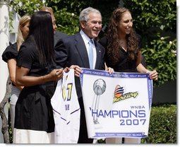 President George W. Bush, joined by Diana Taurasi, left, and Cappie Pondexter, is presented a Phoenix Mercury Championship banner and a personalized team jersey Monday, June 23, 2008, during the 2007 WNBA Champions, the Phoenix Mercury, visit to the White House. White House photo by Eric Draper