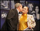 "President George W. Bush gives a kiss on the cheek to Edith Espinoza, Administrative Assistant, Chicano Federation, after introducing him at the Office of Faith-Based and Community Initiatives National Conference Thursday, June 26, 2008, in Washington, D.C. The President opens his remarks, ""How beautiful was that? From being a homeless mother of two to introducing the President of the United States. There has to be a higher power. I love being with members of the armies of compassion, foot soldiers in helping make America a more hopeful place. Every day you mend broken hearts with love. You mend broken lives with hope. And you mend broken communities with countless acts of extraordinary kindness."" White House photo by Chris Greenberg"