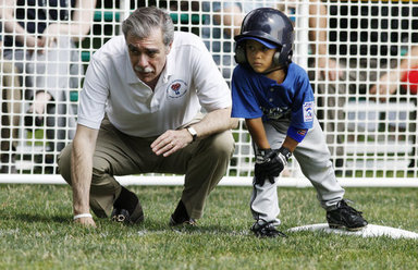 U.S. Secretary of Commerce Carlos Gutierrez coaches a player on third base of the Jose M. Rodriguez Little League Angels of Manati, Puerto Rico, during the 2008 Tee Ball on the South Lawn Season Opener Monday, June 30, 2008, on the South Lawn of the White House. White House photo by Eric Draper