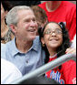 President George W. Bush poses for a photo with a fan in the stands Monday, June 30, 2008, during the opening game of the 2008 Tee Ball season between the Cramer Hill Little League Red Sox of Camden, N.J., and the Jose M. Rodriguez Little League Angels of Manati, Puerto Rico, on the South Lawn of the White House. White House photo by Chris Greenberg