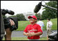A player with the Cramer Hill Little League Red Sox of Camden, N.J., is the center of media attention on the South Lawn of the White House after playing Monday, June 30, 2008, in the opening game of the 2008 Tee Ball on the South Lawn, with his teammates against the Jose M. Rodriguez Little League Angels of Manati, Puerto Rico. White House photo by Chris Greenberg