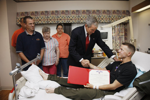 President George W. Bush shakes hands with U.S. Marine Corps Pfc. Charles Cozart of Arizona City, Ariz., Thursday, July 3, 2008, after awarding Cozart with a Purple Heart medal and citation at the National Naval Medical Center in Bethesda, Md. Joining the ceremony, background, are his father and mother, Kevin and Sharon Cozart, and his grandparents, Arthur and Betty Cozart. White House photo by Eric Draper