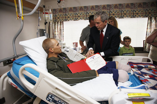 President George W. Bush awards a Purple Heart and citation to U.S. Marine Corps Sgt. Justin Clenard of Tehachapi, Calif., Thursday, July 3, 2008, at the National Naval Medical Center in Bethesda, Md. Looking on is Sgt. Clenard's father, Christopher Clenard, his stepmother, Kerrin Clenard, and his brother, Kevin Clenard. At far right is his mother, Lori Sander. White House photo by Eric Draper