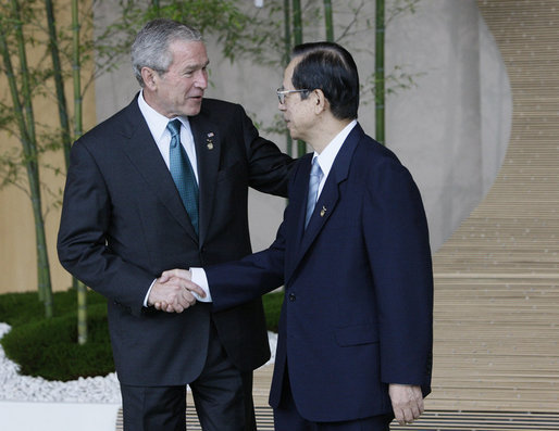 Prime Minister Yasuo Fukuda of Japan greets President George W. Bush as he arrives Monday, July 7, 2008, for the official G8 family photo in the grand lobby of the Windsor Hotel Toya Resort and Spa in Toyako, Japan. White House photo by Eric Draper