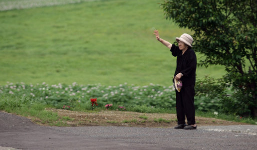 A resident of Makkari waves as the G-8 Spouses pass by en route Tuesday, July 8, 2008, to Hokkaido Marche, a farmer's market, on Japan's northern island of Hokkaido, site of the 2008 G-8 Summit. White House photo by Shealah Craighead