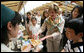 Mrs. Laura Bush tastes a sampling of the food at the Hokkaido Marche farmer's market in Makkari Village Tuesday, July 8, 2008, as part of the G-8 Spouses Program. The small village on the northern Japanese island of Hokkaido is known for its lilies and its potatoes, and the market, organized especially for the occasion of the G-8 Summit, showcased locally grown produce. White House photo by Shealah Craighead