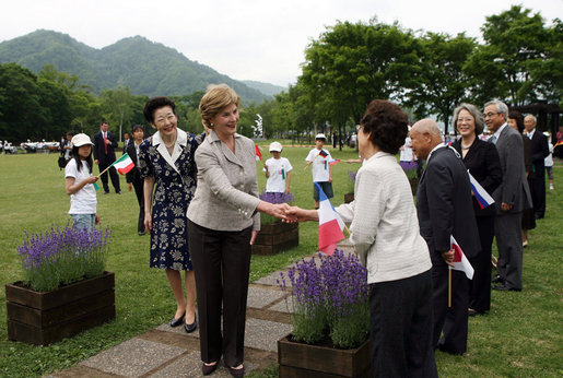 Mrs. Laura Bush, accompanied by Mrs. Kiyoko Fukuda, spouse of the Prime Minister of Japan, left, is greeted as she arrives to the Toyako New Mount Showa Memorial Park for a ceremonial tree planting ceremony with other G-8 spouses Wednesday, July 9, 2008, in Hokkaido, Japan. White House photo by Shealah Craighead