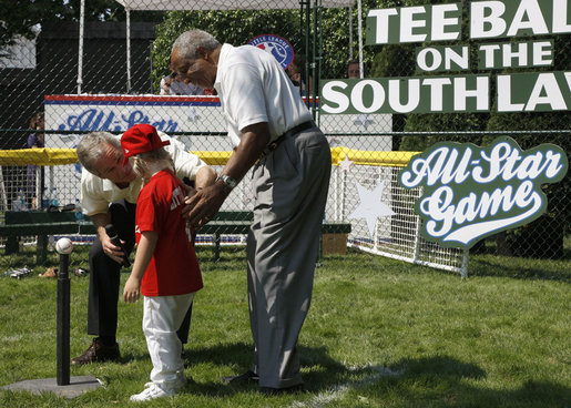 President George W. Bush and Hall of Famer Frank Robinson offer words of encouragement to 8-year-old Shelby Shayler of the Little League Challenger Division in Norfolk, Va., Wednesday, July 16, 2008, as she places a ball on the tee to start the first game of a doubleheader on the South Lawn of the White House. White House photo by Eric Draper