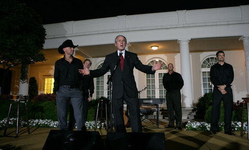 "With Kenny Chesney listening in, President George W. Bush addresses guests in the Rose Garden Wednesday, July 16, 2008, following the Social Dinner in Honor of Major League Baseball. The President told his audience, """"It doesn't get much better than this – country music in the Rose Garden and celebrating baseball."" White House photo by Chris Greenberg"