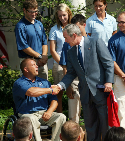 President George W. Bush shakes hands with Scott Winkler, 2008 U.S. Paralympics Track and Field team member, during a photo opportunity with the 2008 United States Summer Olympic Team Monday, July 21, 2008, in the Rose Garden of the White House. White House photo by Shealah Craighead