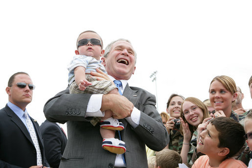 President George Bush shares a laugh as he holds baby while greeting military personnel and families upon departure from the Greater Peoria Regional Airport - Air National Guard Ramp in Peoria, IL Friday, July 25, 2008. White House photo by Chris Greenberg