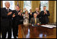 President George W. Bush is applauded after signing H.J. Res. 93, the Renewal of Import Restrictions on Burma and H.R. 3890, the Tom Lantos Block Burmese JADE Act of 2008, Tuesday, July 29, 2008 in the Oval Office of the White House. Applauding President Bush are, from left, Rep. Don Manzullo, R-Ill.; Rep. Chris Smith, R-N.J.; Mrs. Laura Bush, Annette Lantos, widow of Rep. Tom Lantos; Lantos grandson, Shiloh Tillemann; Rep.Rush Holt, D-N.J.; Rep. Joe Pitts, R-Pa.; and Rep. Peter King, R-N.Y. White House photo by Eric Draper
