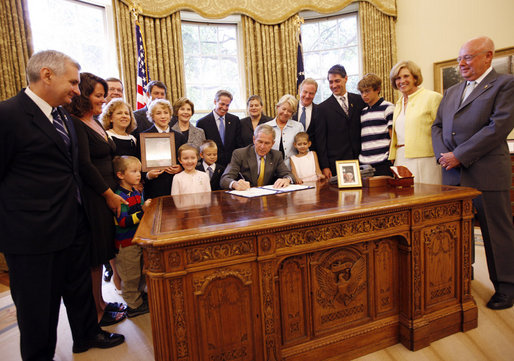 President George W. Bush signs the Caroline Pryce Walker Conquer Childhood Cancer Act of 2008 Tuesday, July 29, 2008, in the Oval Office of the White House. President Bush is joined at his desk by Mrs. Laura Bush, HHS Secretary Mike Leavitt, the Lewis family, the Adams family, the Haight family, the Rech family, and Congressional representatives Sen. Jack Reed D-RI; Minnesota Senator Norm Coleman; Rep. Deborah Pryce R-OH; and Rep. Chris Van Hollen D-MD; and CureSearch's Dr. Gregory Reaman. White House photo by Eric Draper