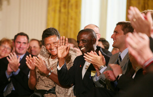 HIV/AIDS activist Mohamed Kalyesubula of Uganda waves to acknowledge the applause of guests, joined by fellow HIV/AIDS activist nurse Agnes Nyamayarwo of Uganda, left, both honored by President George W. Bush Wednesday, July 30, 2008 in the East Room of the White House, at the signing ceremony of H.R. 5501, the Tom Lantos and Henry J. Hyde United States Global Leadership Against HIV/AIDS, Tuberculosis and Malaria Reauthorization Act of 2008. White House photo by Joyce N. Boghosian