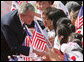 President George W. Bush pauses to greet school children Wednesday, Aug. 6, 2008, during arrival ceremonies at the Blue House, the residence of President Myung-bak Lee of the Republic of Korea, in Seoul. White House photo by Chris Greenberg