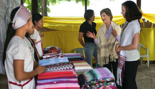 Mrs. Laura Bush and daughter Ms. Barbara Bush look over the weaving done by refugee women at the Mae La Refugee Camp at Mae Sot, Thailand, on Aug. 7, 2008. This traditional Karen craft helps the refugees make money and can be bought via the Internet through consortiums that work with the women in the camp which houses at least 39,000 Burmese. White House photo by Shealah Craighead