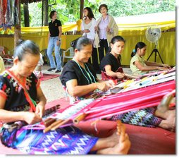 Mrs. Laura Bush and daughter Ms. Barbara Bush try on shawls created by weavers carrying on the traditional Karen ethnic craft at the Mae La Refugee Camp at Mae Sot, Thailand. In her August 7, 2008 comments, Mrs. Bush pointed out that the weavings are done to help generate money for the refugees and can be purchased via the Internet through consortiums that work with women at the camp. The camp houses at least 39,000 refugees waiting for a safe time to return to their home country. Many have decided the wait of 20 years has been too long and have immigrated to the United States and other countries. White House photo by Shealah Craighead