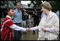 Mrs. Laura Bush is greeted as she prepares to enter a school at the Mae La Refugee Camp in Mae Sot, Thailand, where an English grammar class is being taught. Her Aug. 7, 2008 visit to the camp, which houses at least 39,000 Burmese refugees, highlighted the plight of a people who have struggled since the Aug. 8, 1988 crackdown that created dire conditions in their country 20 years ago. Many have moved to the United States or other countries such as Canada, New Zealand or the Netherlands. Mrs. Bush encouraged other countries to help the Burmese as well. White House photo by Shealah Craighead