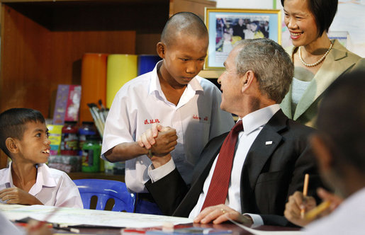 President George W. Bush connects with children at the Human Development Foundation - Mercy Centre in Bangkok on August 7, 2008. The non-profit group helps residents of the slums of Bangkok by building and operating schools and working on family health and welfare issues, such as AIDS and street children's rights. After visiting the school, President Bush participated in a briefing on disaster relief efforts in Burma at the Ambassador's residence and then met with Burmese activists and media before heading to China. White House photo by Eric Draper