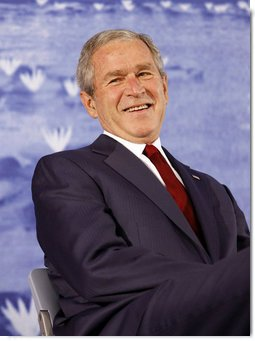 President George W. Bush smiles during an introduction by his father, former President George H.W. Bush Friday, Aug. 8, 2008, during the dedication of the United States Embassy in Beijing. White House photo by Eric Draper