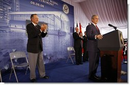 "President George W. Bush acknowledges applause after being introduced by former President George H.W. Bush Friday, Aug. 8, 2008, during dedication ceremonies at the U.S. Embassy in Beijing. Said the President, ""This has got to be a historic moment: father and son, two Presidents, opening up an embassy. I suspect it's the first, although I must confess I haven't done a lot of research into the itinerary of the Adams boys."" White House photo by Eric Draper"