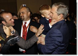 President George W. Bush is hugged by a young boy Friday, Aug. 8, 2008, during a greeting at the U.S. Embassy in Beijing.  White House photo by Eric Draper