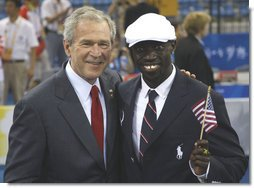President George W. Bush poses for a photo with U.S. Olympic runner Lopez Lomong Friday, Aug. 8, 2008, in Beijing prior to Opening Ceremonies of the 2008 Summer Olympic Games. Lopez Lomong, a survivor of the violence in his native Sudan, now a U.S. citizen, was selected by his teammates to lead the U.S. Olympic team into Olympic National Stadium carrying the United States Flag at the Opening Ceremony. White House photo by Eric Draper