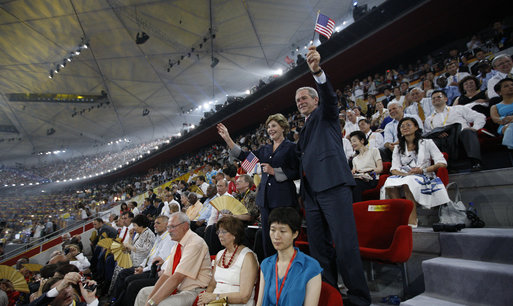 President George W. Bush waves an American flag as he and Mrs. Laura Bush stand and cheer during the entrance of the U.S. athletes into China's National Stadium Friday, Aug. 8, 2008, in Beijing. White House photo by Eric Draper
