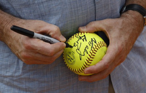 President George W. Bush autographs softball during the U.S. Women's Softball practice Saturday, Aug. 9, 2008, at Fengtai Complex in Beijing. White House photo by Eric Draper