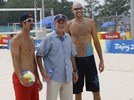 President George W. Bush pauses with U.S. Men's Beach Volleyball's Todd Rogers, left, and Philip Dalhausser as he visited the practice session Saturday, Aug. 9, 2008, at Beijing's Chaoyang Park prior to their first matches of the 2008 Summer Olympic Games. White House photo by Eric Draper