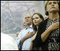 President George W. Bush, daughter Barbara Bush and Mrs. Doro Koch, the President's sister, stand for the playing of the U.S. national anthem Sunday, Aug. 10, 2008, during the medal ceremony honoring gold-medalist Michael Phelps. The U.S. Olympian won his first event, the 400-meter Individual Medley, in a record time of 4:3.84. White House photo by Eric Draper