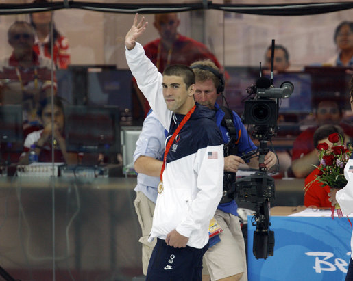 U.S. gold medalist Michael Phelps waves as he leaves poolside Sunday, Aug. 10, 2008, after winning the 400-meter Individual Medley in world-record time at the 2008 Summer Olympics in Beijing. White House photo by Eric Draper