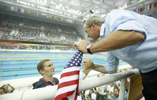President George W. Bush shakes hands with U.S. swimmer Larsen Jensen after the 22-year-old won his bronze medal in the 400-meter freestyle Sunday, Aug. 10, 2008, at the 2008 Summer Olympics. White House photo by Eric Draper