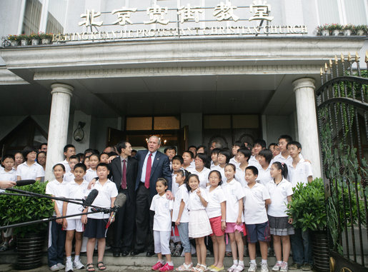 "Standing with the Kuanjie Summer Vacation School Choir and Pastor Meng Maoru, President George W. Bush delivers a statement outside Beijing Kuanjie Protestant Christian Church in Beijing Sunday, Aug. 10, 2008. Said the President, ""Laura and I just had the great joy and privilege of worshiping here in Beijing, China. You know, it just goes to show that God is universal, and God is love, and no state, man or woman should fear the influence of loving religion."" White House photo by Chris Greenberg"