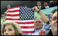 President George W. Bush displays an American flag as he cheers on the U.S. Olympic Swimming Team Sunday, Aug. 10, 2008, at the National Aquatics Center in Beijing. White House photo by Shealah Craighead
