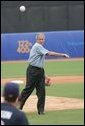 President George W. Bush throws out the first pitch to the U.S. Olympic men's baseball team catcher Lou Marson before a practice game against the Chinese Olympic men's baseball team Monday, Aug. 11, 2008, at the 2008 Summer Olympic Games in Beijing. White House photo by Chris Greenberg