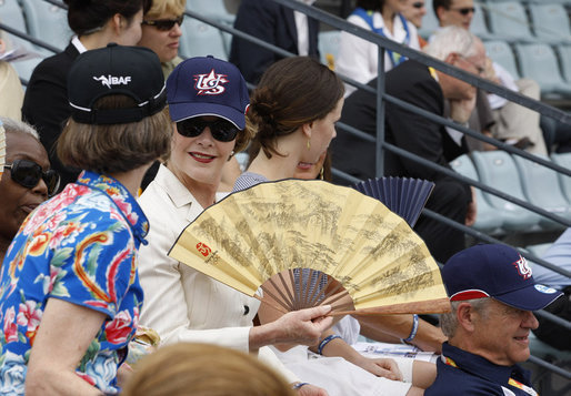 Mrs. Laura Bush wearing a U.S. Olympic baseball team hat uses a fan to keep cool as she watches the U.S. Olympic men's baseball team play a practice game against the Chinese Olympic men's baseball team Monday, Aug. 11, 2008, at the 2008 Summer Olympic Games in Beijing. White House photo by Eric Draper