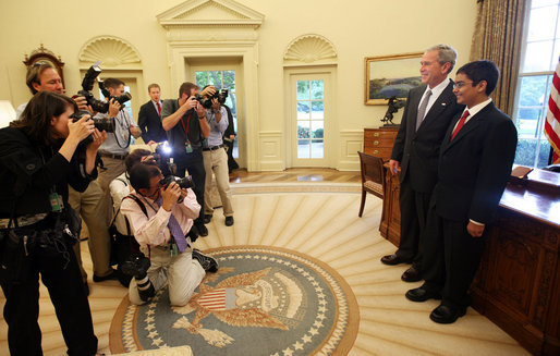 "President George W. Bush stands with Sameer Mishra, 14, of Lafayette, Ind., during his visit Wednesday, Aug. 13, 2008, to the Oval Office of the White House. The teen was named the 2008 Scripps National Spelling Bee Champion in the 16th round after correctly spelling the word ""guerdon,"" meaning a reward or recompense). White House photo by Joyce N. Boghosian"