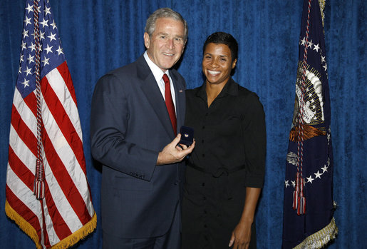 President George W. Bush stands with Keela Carr, a 35-year-old fitness and athletic trainer, shortly after his arrival Wednesday, Aug. 20, 2008, in Orlando, Florida. Ms. Carr was recognized by the U.S. Army's Freedom Team Salute Program and named its 500th Volunteer Ambassador in recognition of her 2008 2,700-mile, trans-America Journey of a Thousand Thanks to honor and thank all soldiers and veterans. White House photo by Eric Draper