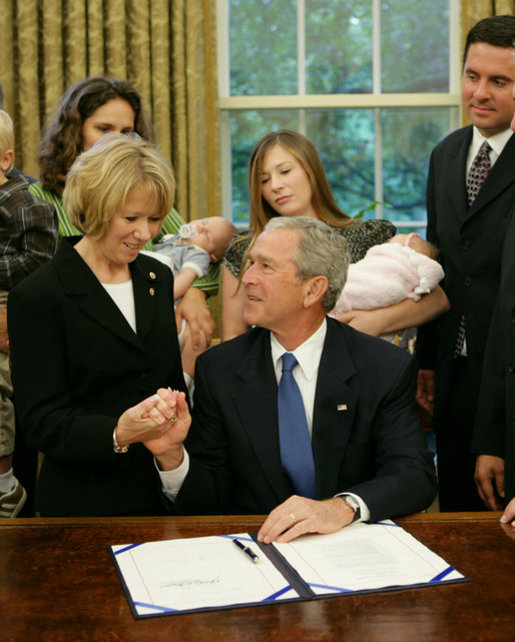 President George W. Bush holds the hand of Peggy Hubbard, mother of the Hubbard brothers, after signing H.R. 6580, The Hubbard Act, Aug. 29, 2008, in the Oval Office of the White House. The Hubbard Act is named in honor of brothers Jared and Nathan Hubbard , who lost their lives serving our country in Iraq. Their brother, Jason Hubbard was discharged from the Army as a sole survivor but was denied separation benefits. H.R. 6580 will provide sole survivors a number of benefits already offered to other soldiers honorably discharged from military service. White House photo by Chris Greenberg