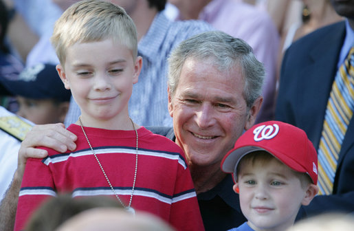 President George W. Bush poses for photos with two youngsters at the Tee Ball on the South Lawn: A Salute to the Troops game Sunday, Sept. 7, 2008, played by the children of active-duty military personnel. White House photo by Chris Greenberg