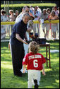 President George W. Bush greets Kassie Frank of Gaithersburg, Md. as he presents her with a baseball Sunday, Sept. 7, 2008, following the final game of Tee Ball on the South Lawn: A Salute to the Troops. White House photo by Grant Miller